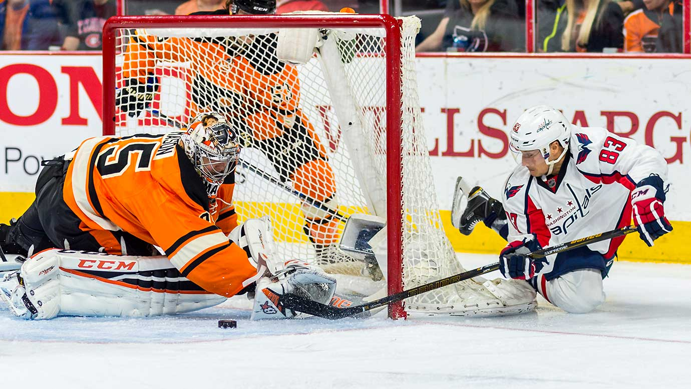 Washington center Jay Beagle shoots around the net as Philadelphia goalie Steve Mason makes the save.