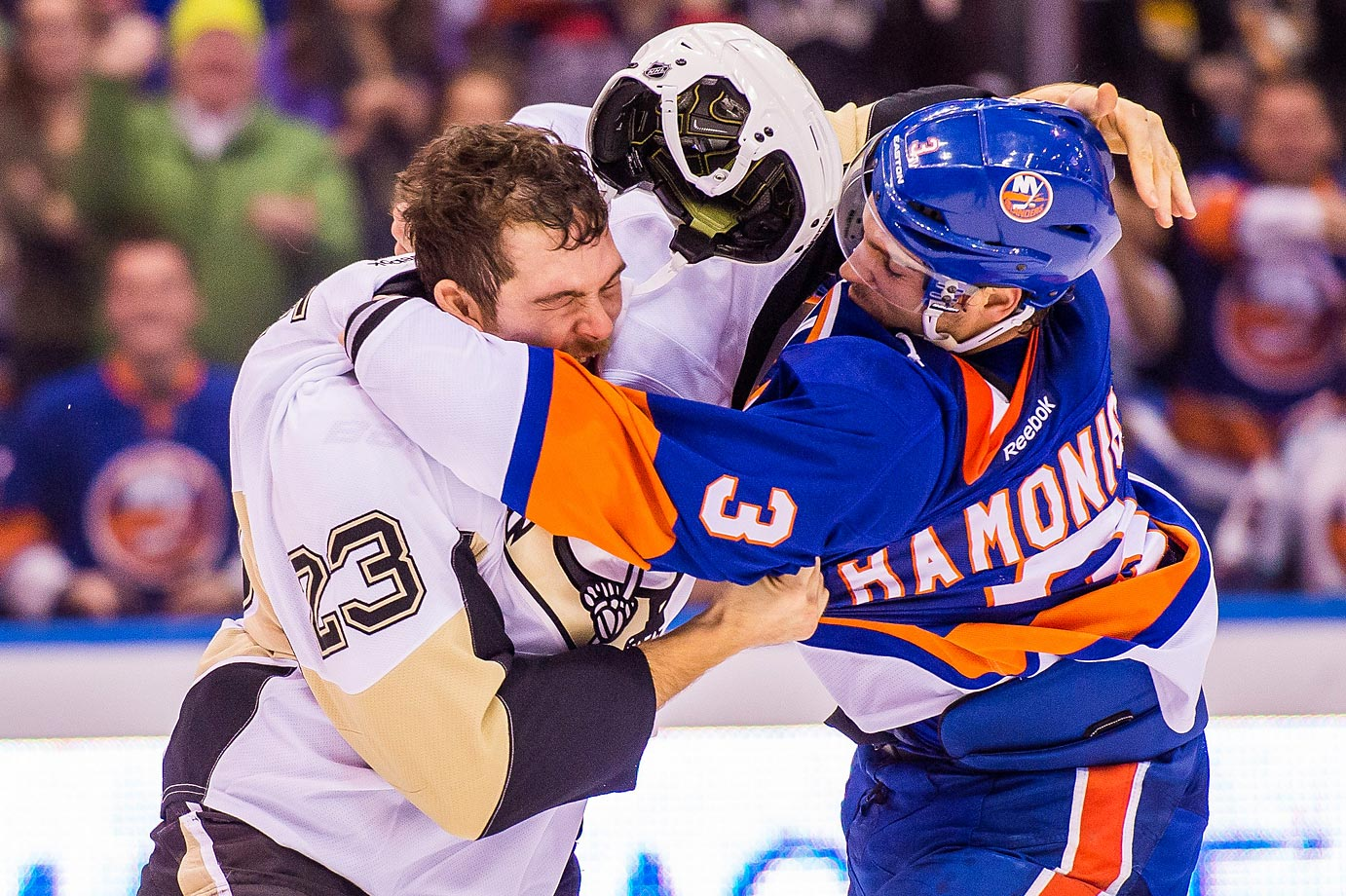 Penguins Steve Downie wrestles with Islanders Travis Hamonic.