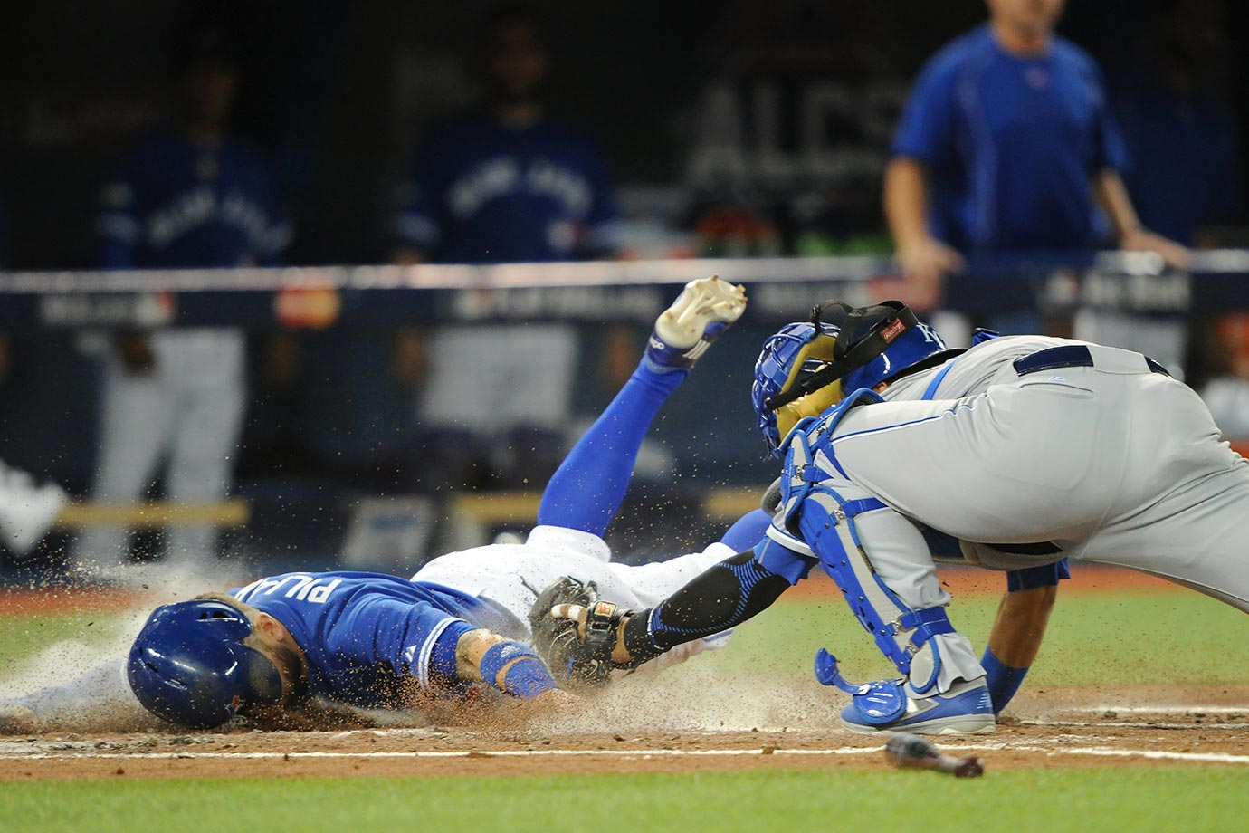 Kevin Pillar of theToronto Blue Jays beats a tag by Salvador Perez of the Kansas City Royals.