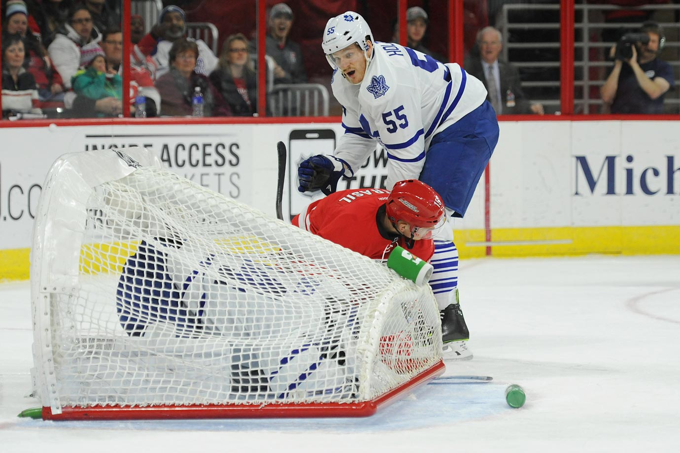James Reimer, the Toronto Maple Leafs goalie, is covered by the goal during a game against the Carolina Hurricanes.  Carolina defeated Toronto 2-1.