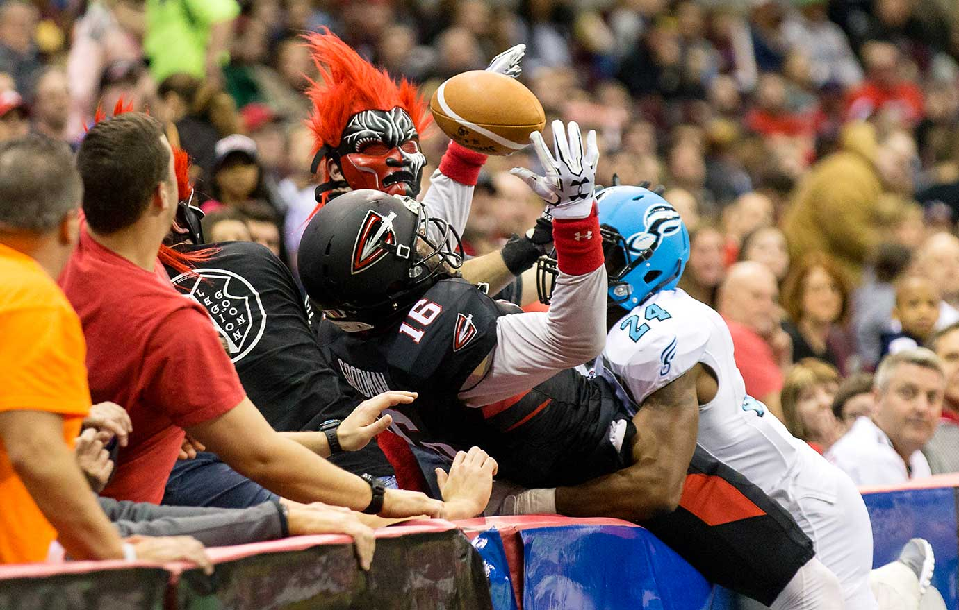 Cleveland Gladiators wide receiver Dominick Goodman tries to make a catch while falling into the stands and being defended by Torez Jones of the Philadelphia Soul.