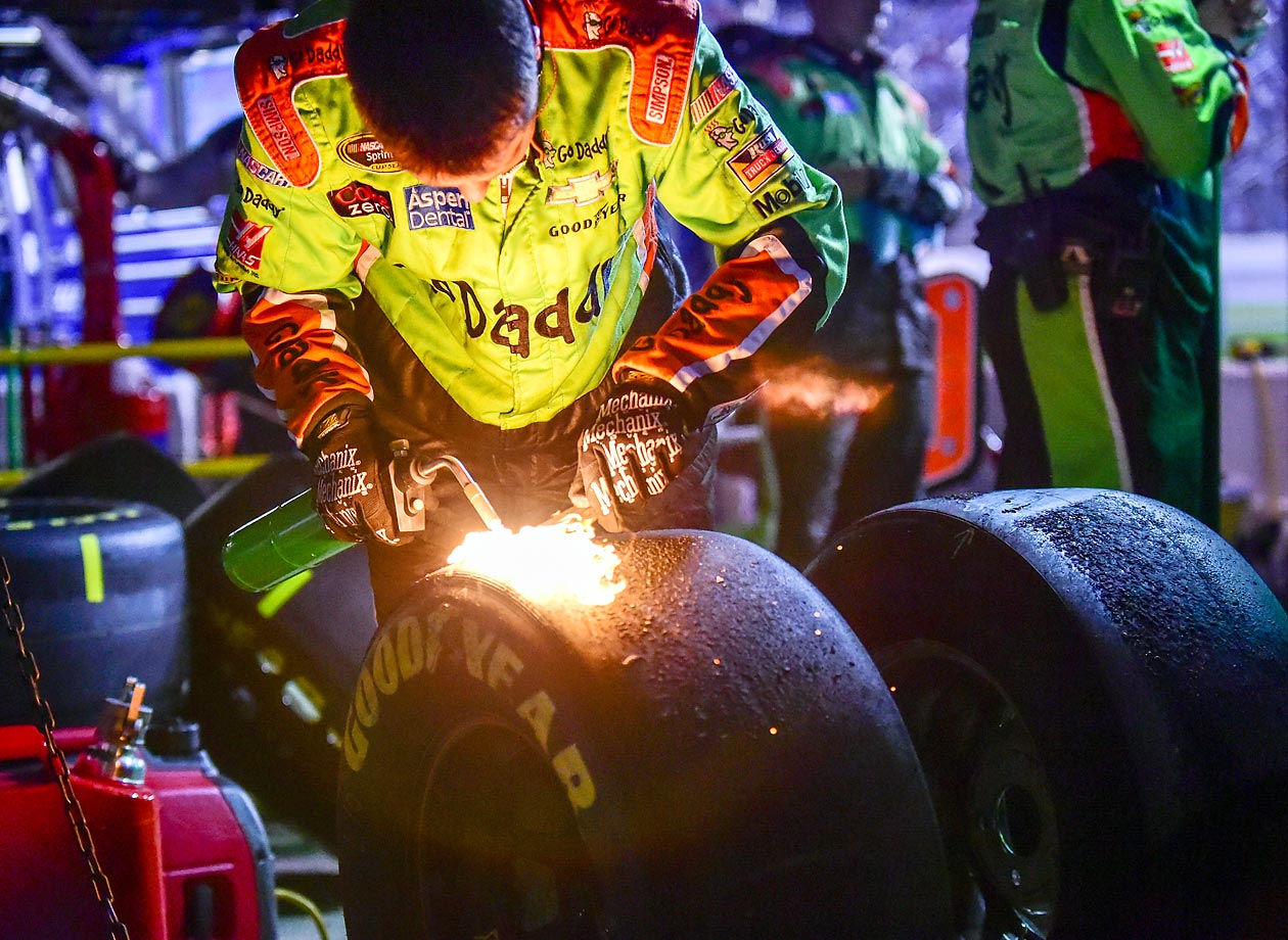 A crew member for Danica Patrick burns excess rubber and debris from a tire for measurements following a pit stop at the Duck Commander 500.