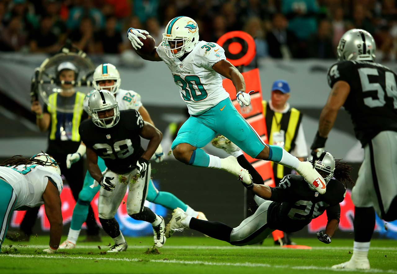 Daniel Thomas of the Miami Dolphins is tackled by Usama Young of the Oakland Raiders.