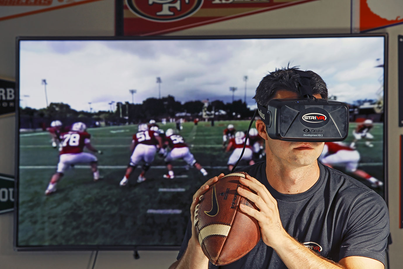 Danny Belch models a virtual reality headset during a photo shoot on July 28, 2015 at STRIVR Lab in Menlo Park, Calif. Developed at Stanford in 2014, the product replays game footage in 3D, and is intended for football film study and review. It is currently in use by several NCAA and NFL teams.