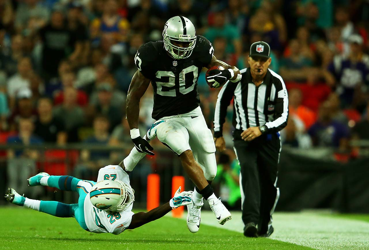 Darren McFadden of the Oakland Raiders is tackled by Will Davis of the Miami Dolphins at Wembley Stadium.