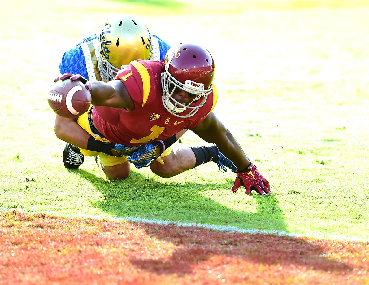 Darreus Rogers of USC reaches for the endzone while being tackled by Nate Meadors of UCLA.