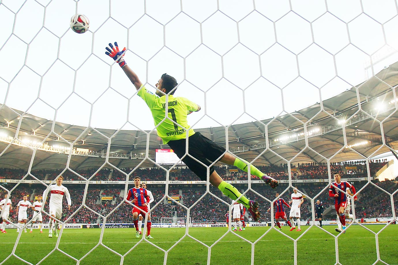David Alaba of Muenchen scores his team's second goal against Sven Ulreich of Stuttgart during the Bundesliga match.