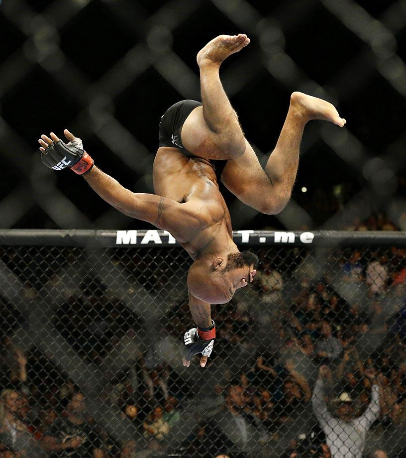 Demetrious Johnson celebrates with a flip after defeating Chris Cariaso in their flyweight mixed martial arts title bout at UFC 178.