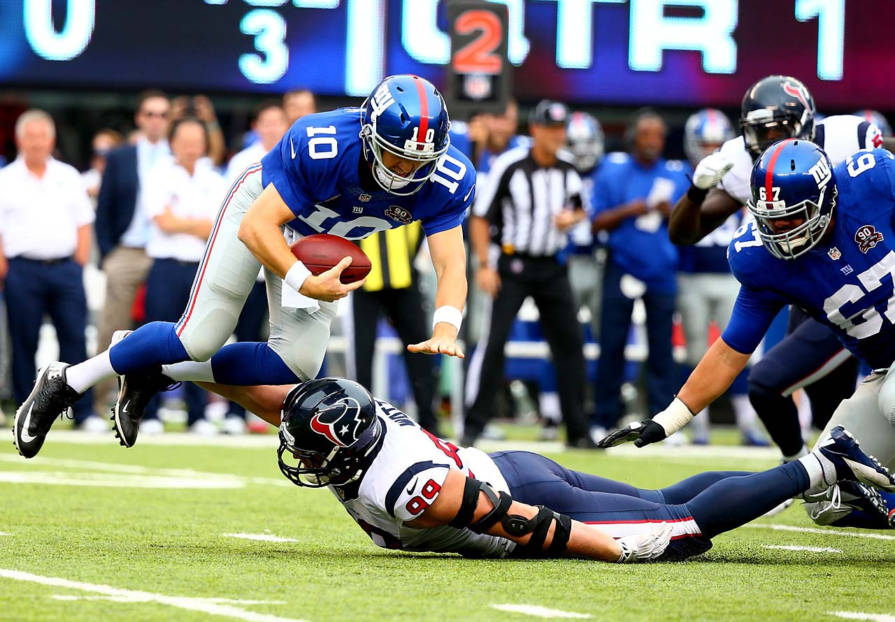 Eli Manning gets tripped up by J.J. Watt.