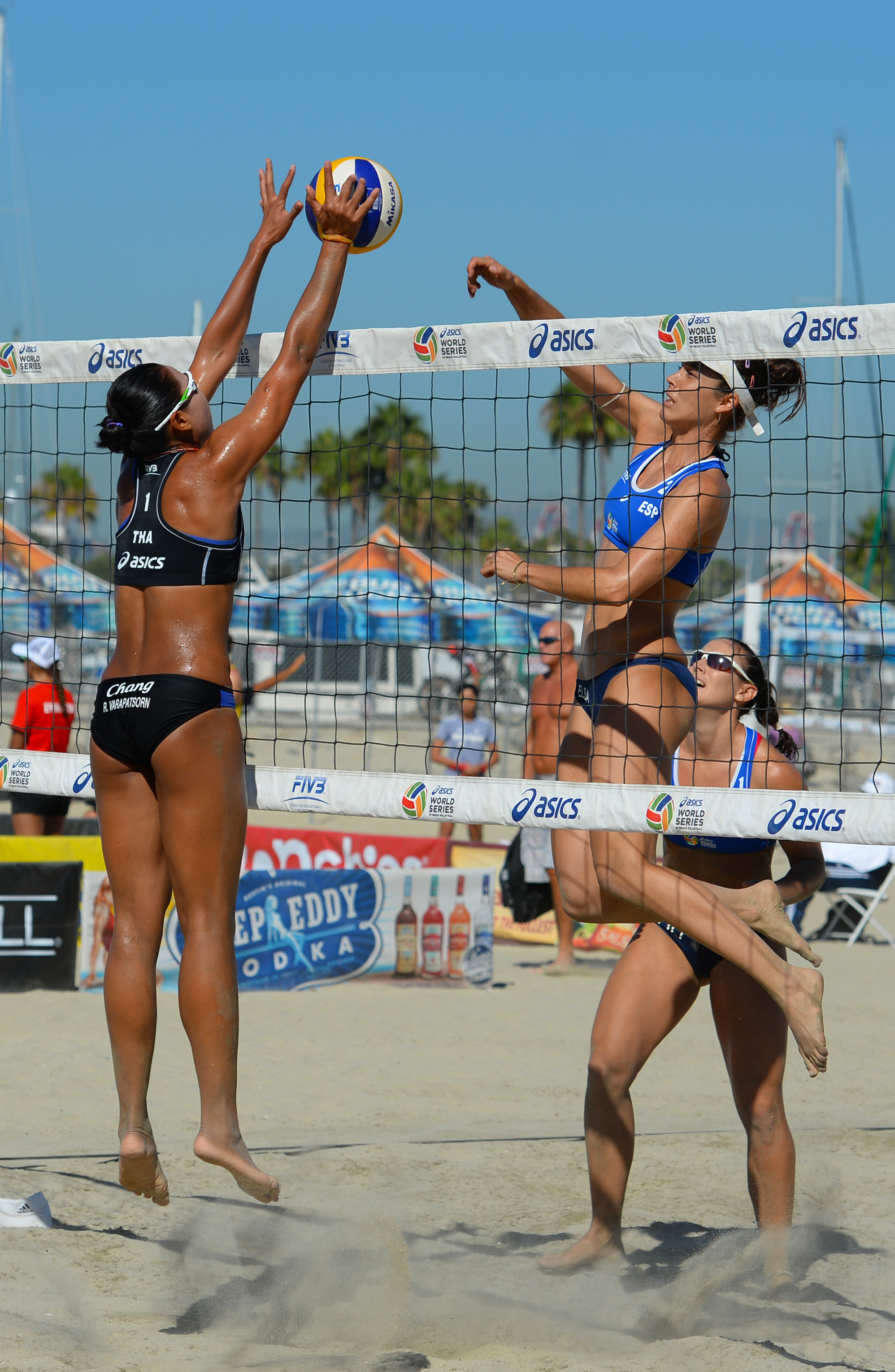 Elsa Baquerizo of Spain (right) spikes the Mikasa against Varapatsorn Radarong of Thailand as Liliana Fernandez of Spain looks on.