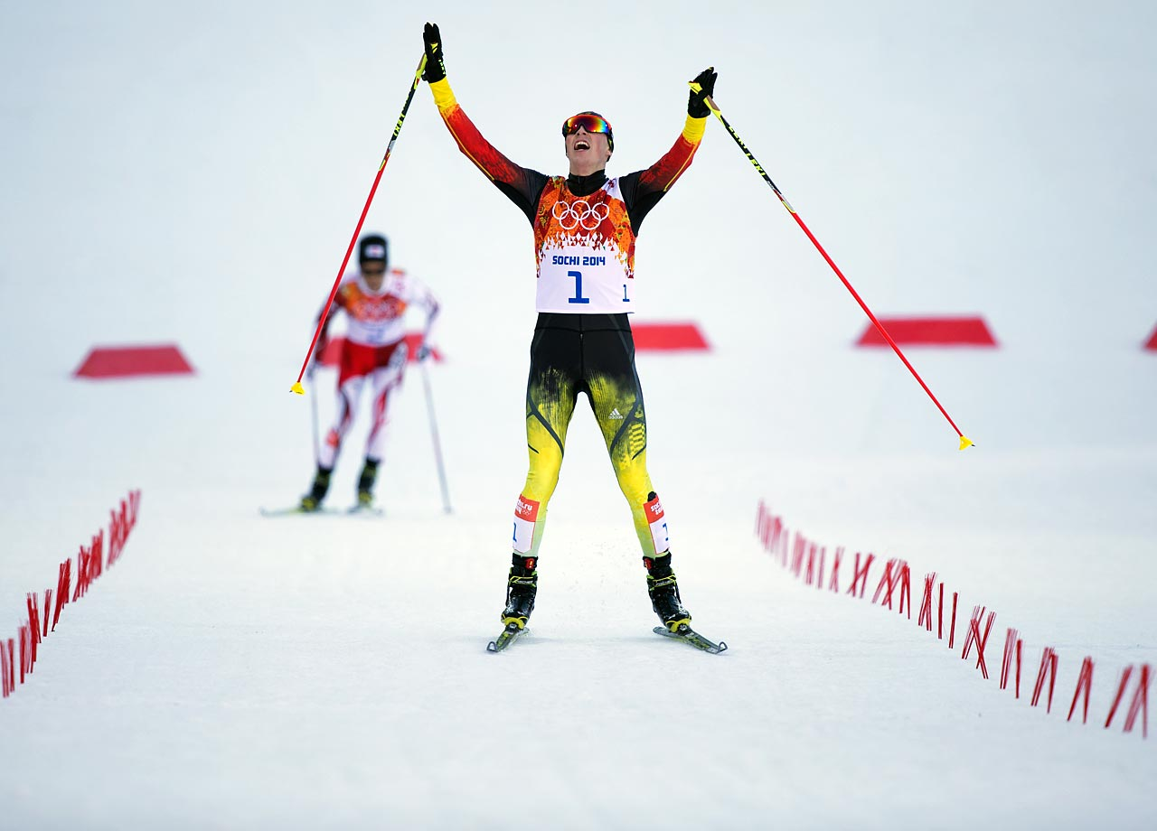 Eric Frenzel of Germany celebrates after he crosses the finish line to win gold ahead of silver medalist Akito Atabe of Japan.