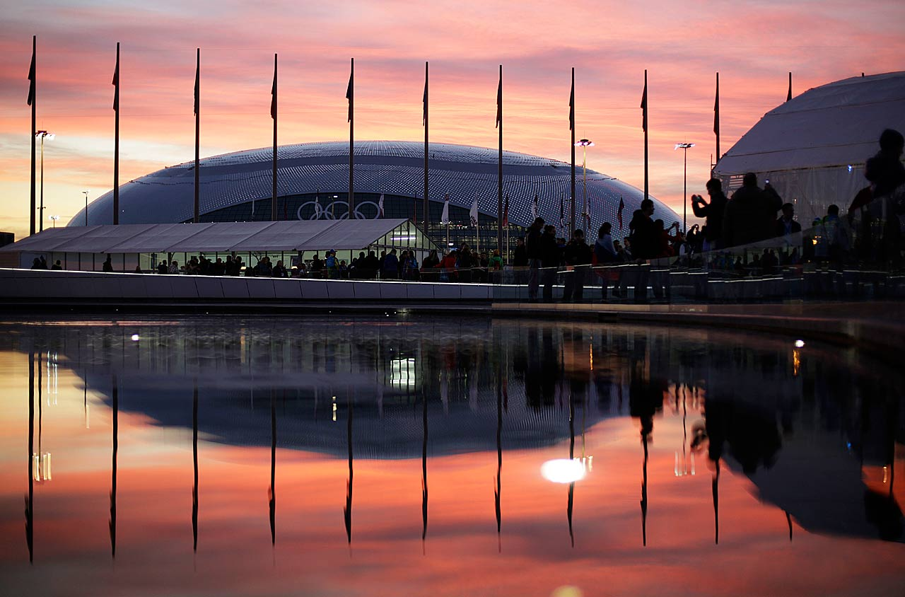 The sun sets as the Bolshoy Ice Dome is reflected in a pool of water underneath the Olympic cauldron.