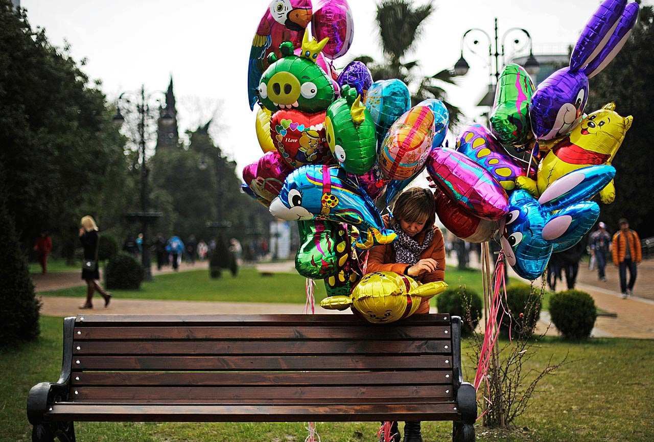 A vendor prepares a bunch of balloons for  display along a pedestrian mall.