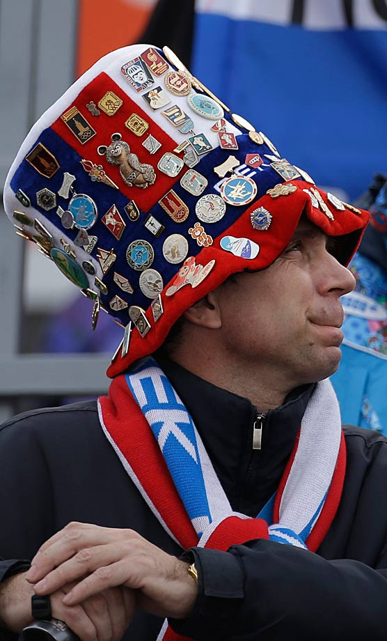 A fan with numerous pins on his hat watches the ski jumping portion of the Nordic combined Gundersen large hill team competition.