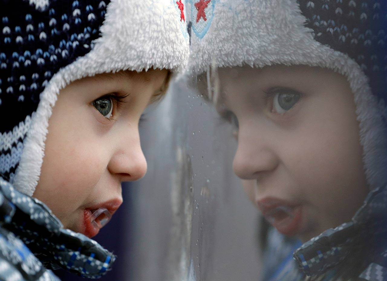 Two-year-old Aleksandr Olegovich looks out a rain-covered gondola window as he travels with his family to watch the women's slalom on Friday, Feb. 21.