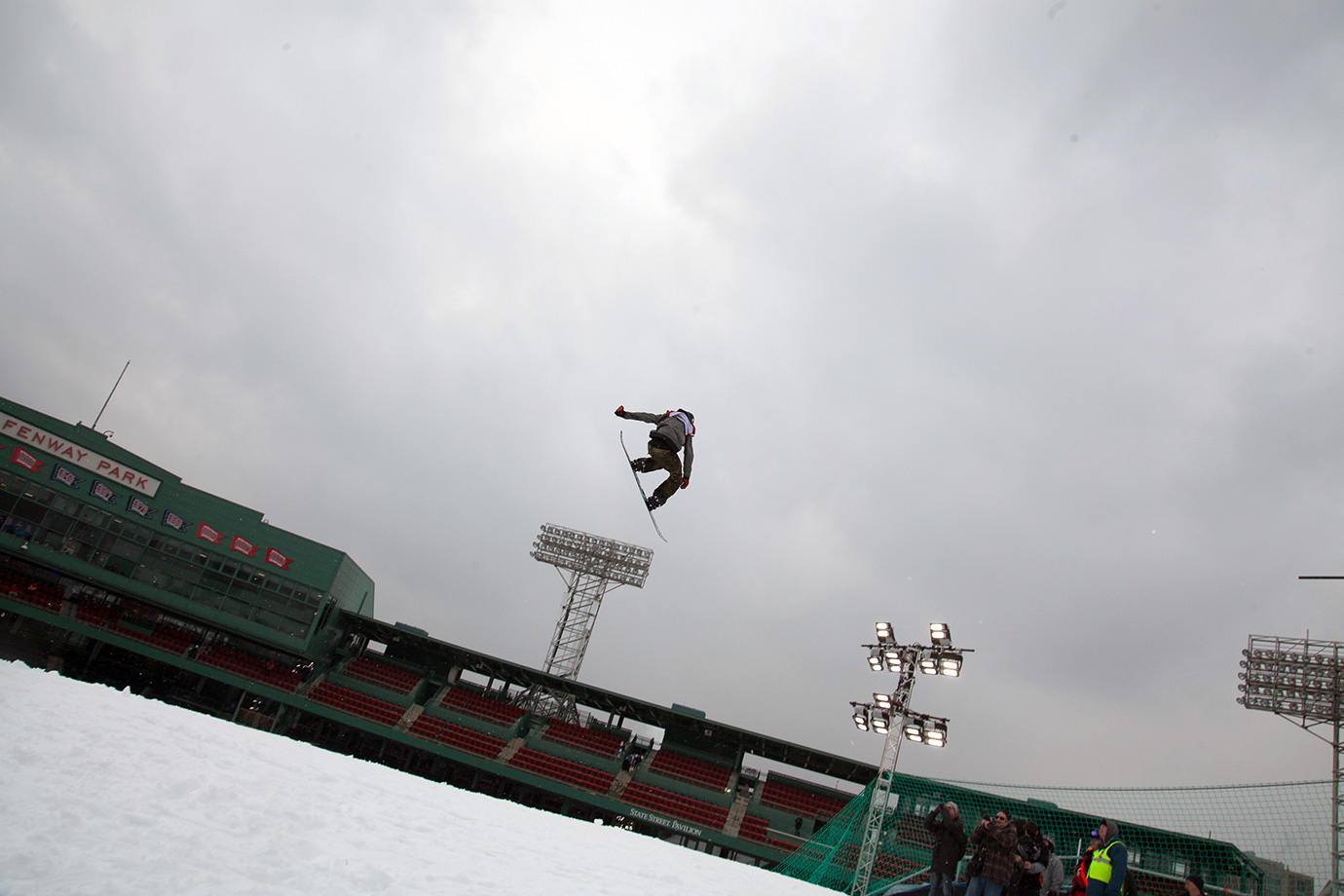A snowboarder rises above the iconic Fenway Park sign during Polartec Big Air practice.