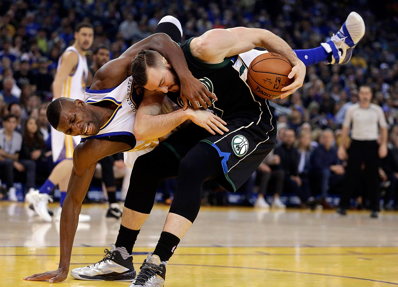 Festus Ezeli of the Golden State Warriors fouls Miles Plumlee of the Milwaukee Bucks.