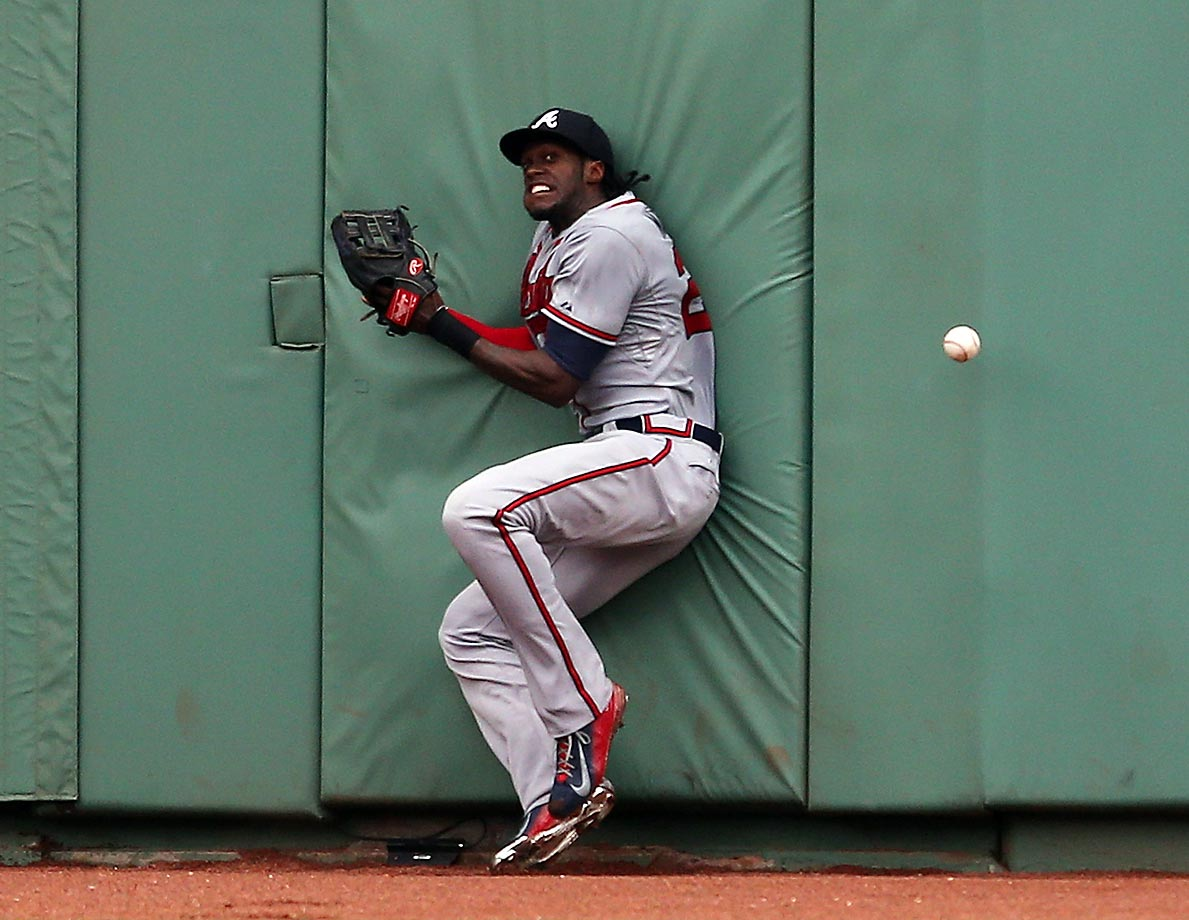 Cameron Maybin of the Atlanta Braves crashes into the wall during a game against the Boston Red Sox.