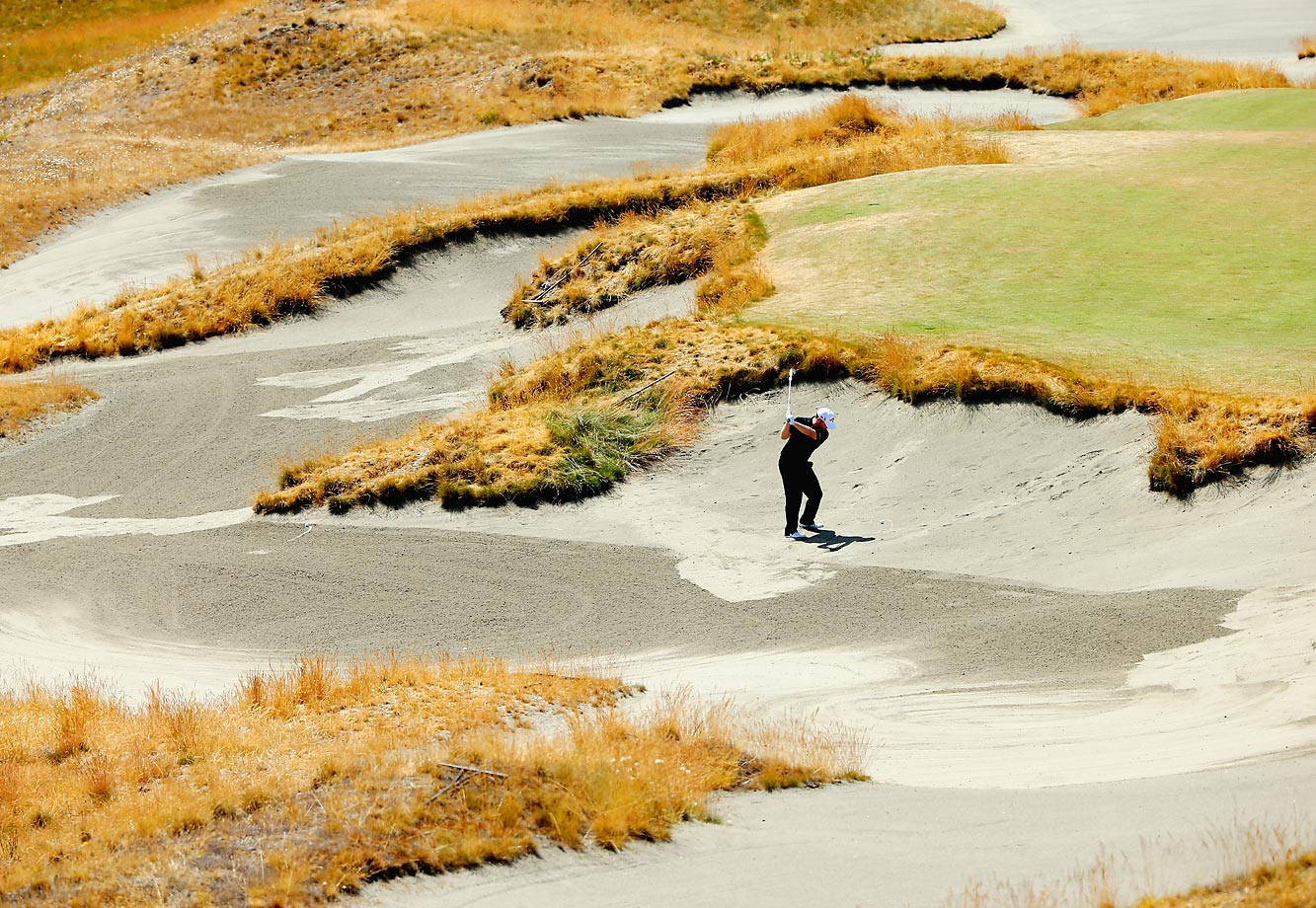 Branden Grace of South Africa hits a shot from a bunker during a practice round at the 115th U.S. Open Championship.