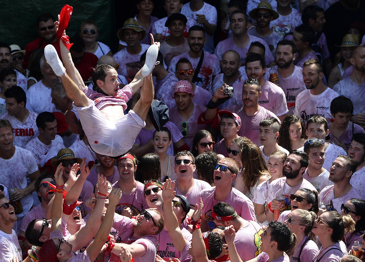 A man is tossed during the 'Chupinazo' (start rocket) celebration that marks the kickoff at noon sharp of the San Fermin Festival in Pamplona, northern Spain. A red-and-white sea of revelers soaked each other with wine in a packed Pamplona square to start off Spain's most famous fiesta, the San Fermin bull-running festival.
