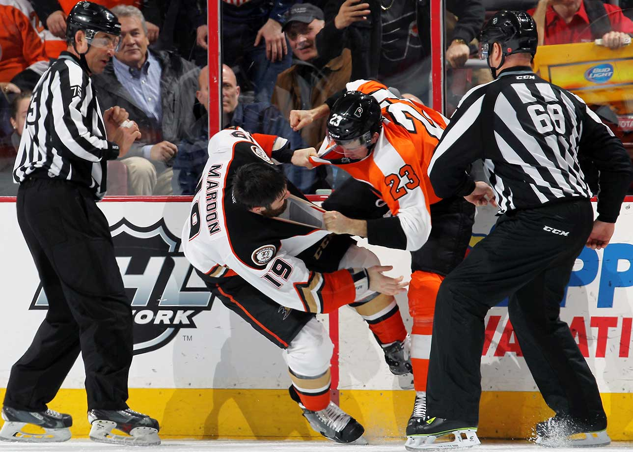 Linesmen Derek Amell and Scott Driscoll watch as Brandon Manning of Philadelphia fights Patrick Maroon of Anaheim.