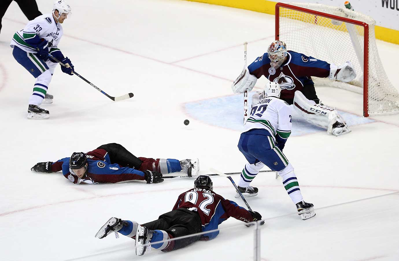 Daniel Sedin of Vancouver passes to Henrik Sedin as Gabriel Landeskog (92) and Erik Johnson (6) of Colorado dive to the ice.  X
