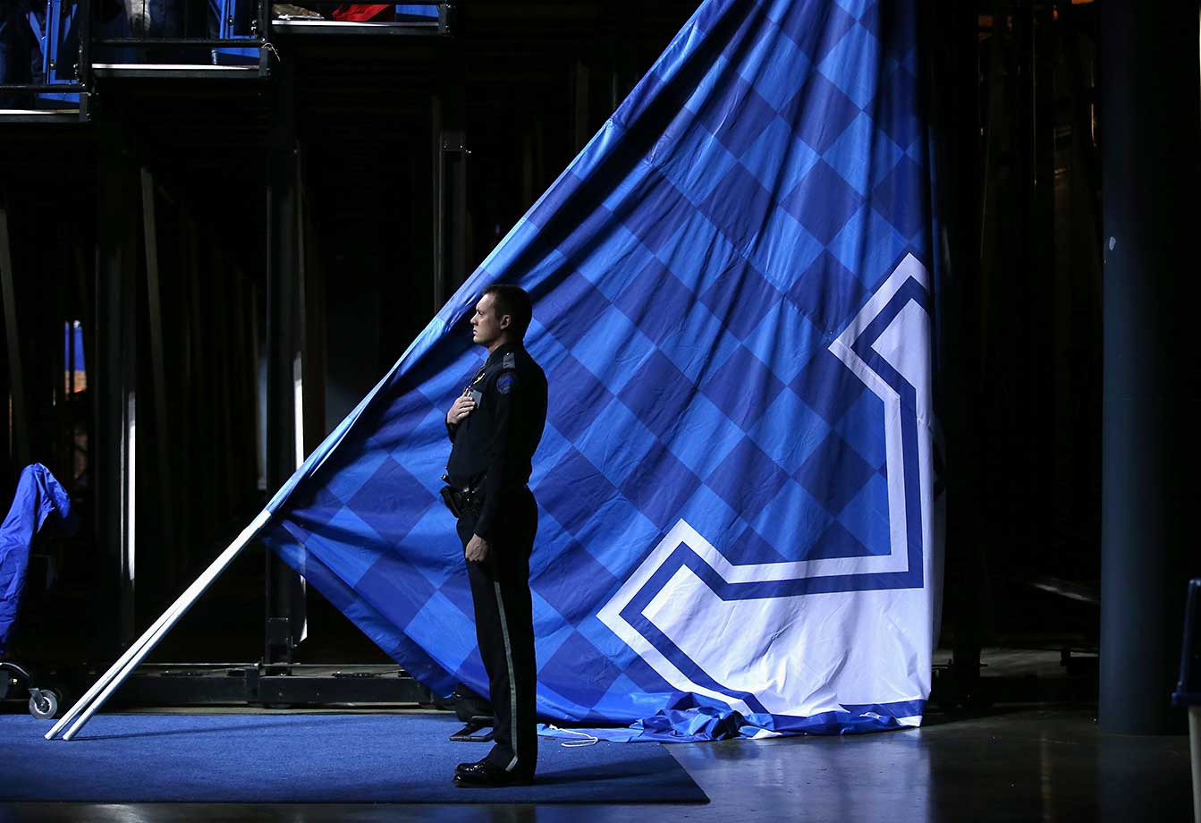 A police officer observes the national anthem before the Kentucky Wildcats game against the Georgia Bulldogs at Rupp Arena.