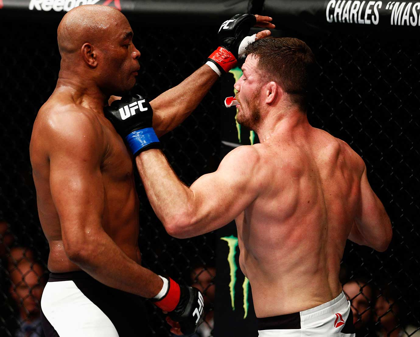 Michael Bisping loses his mouthpiece while punching Anderson Silva during their UFC bout in London.