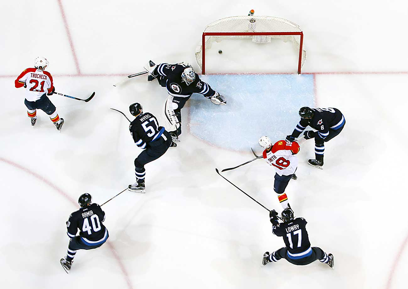 Reilly Smith of Florida Panthers shoots the puck past a sprawling Ondrej Pavelec of Winnipeg.