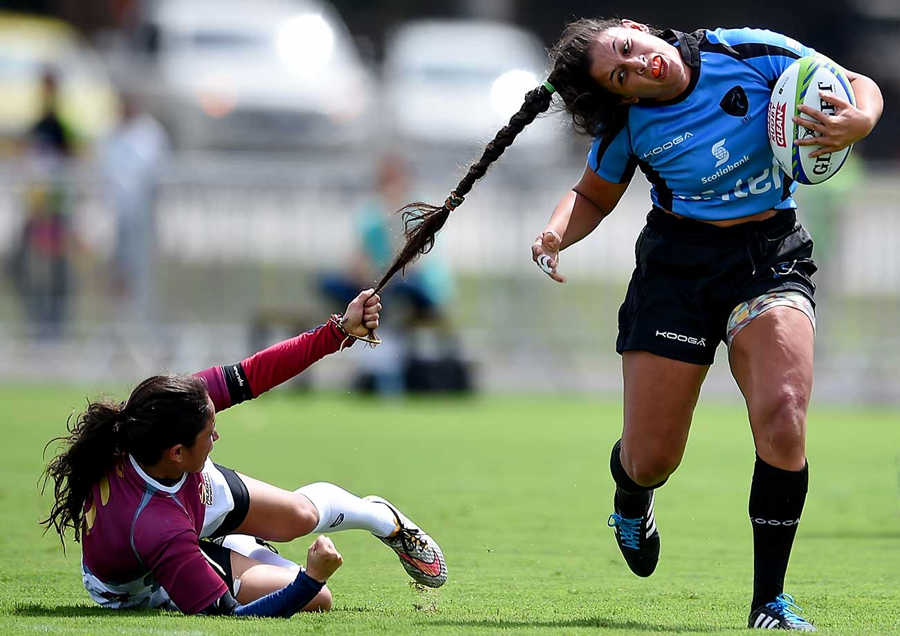 Maryoly Gamez of Brazil tugs at Victoria Rios of Uruguay during the International Women's Rugby Sevens in Rio de Janeiro.