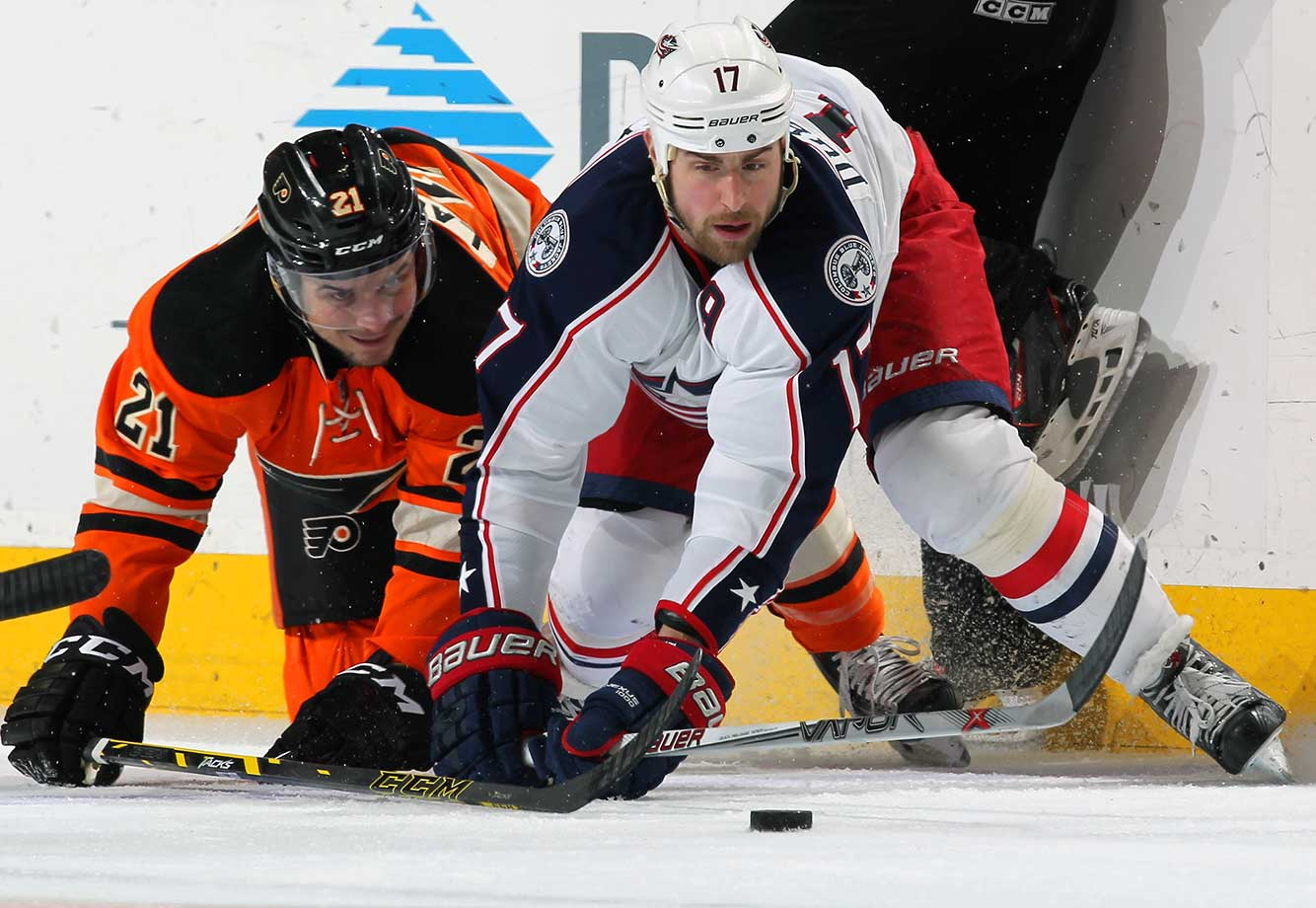 Scott Laughton of Philadelphia and Brandon Dubinsky of Columbus battle for the puck.