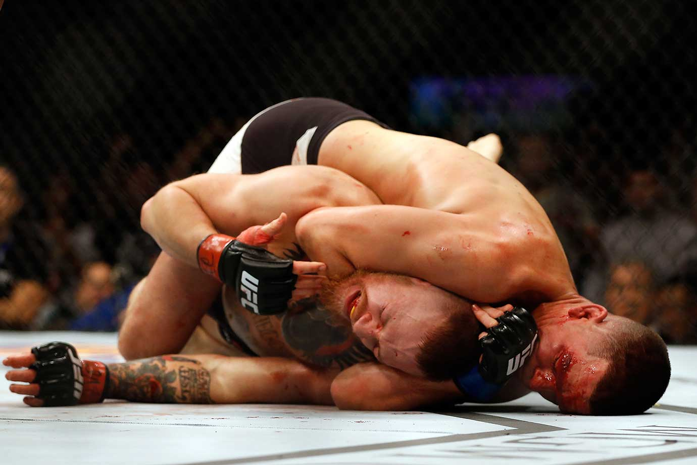 Nate Diaz attempts to submit Conor McGregor of Ireland in their welterweight bout at UFC 196. Diaz ended up winning the fight in the second round.