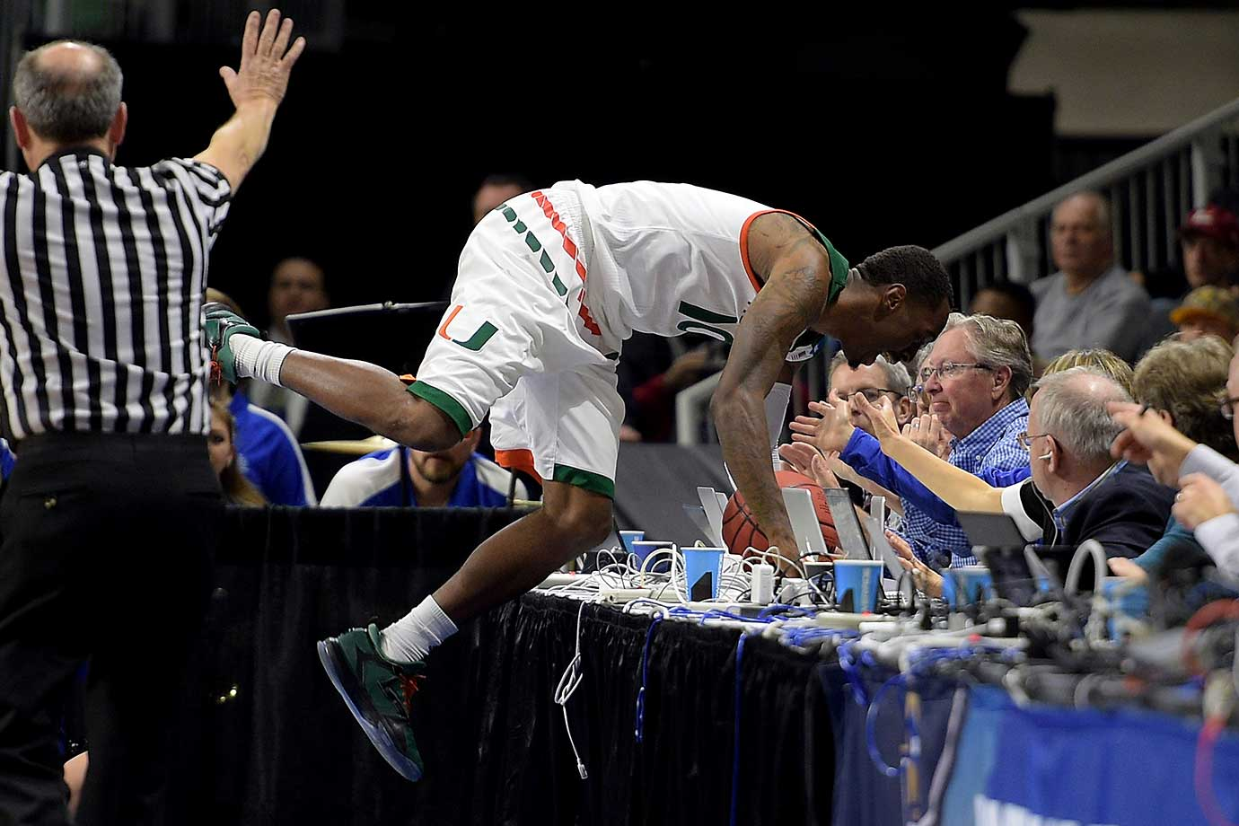 Sheldon McClellan of the Miami Hurricanes crashes into press row after chasing a loose ball.