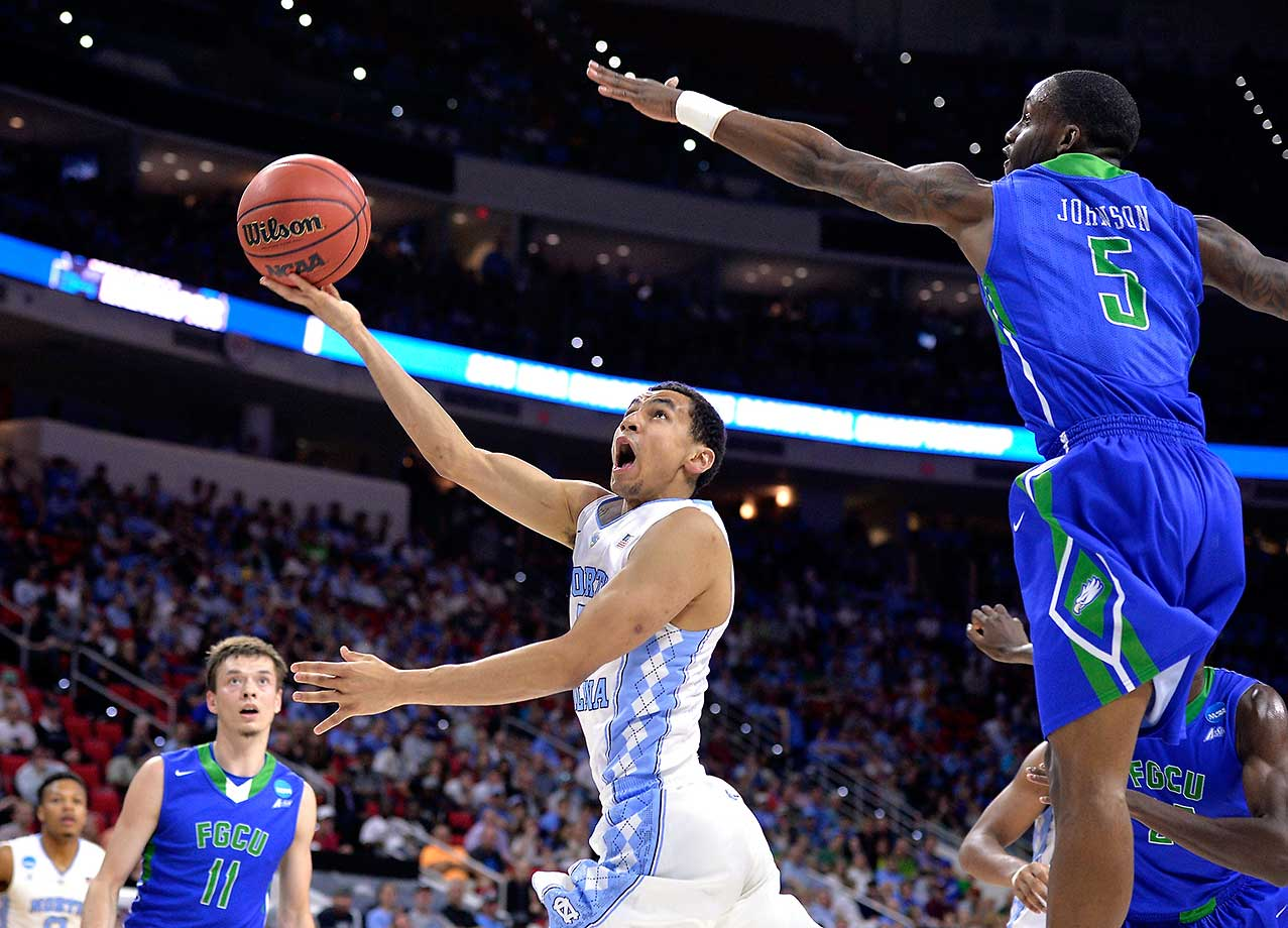 Marcus Paige of the Tar Heels attempts to prevent a blocked shot against the defense of Zach Johnson of Florida Gulf Coast.