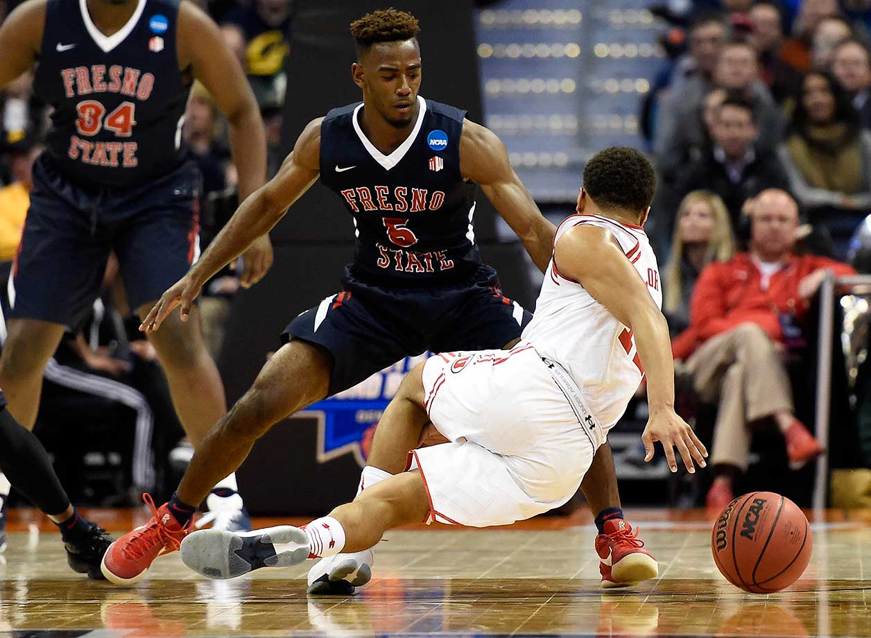 Utah guard Brandon Taylor falls down as Fresno State's Jahmel Taylor defends.