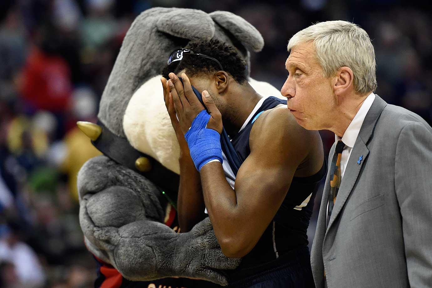 Fresno State's Karachi Edo is hugged by the team's Bulldog mascot as he walks off the court after an 80-69 loss to Utah.