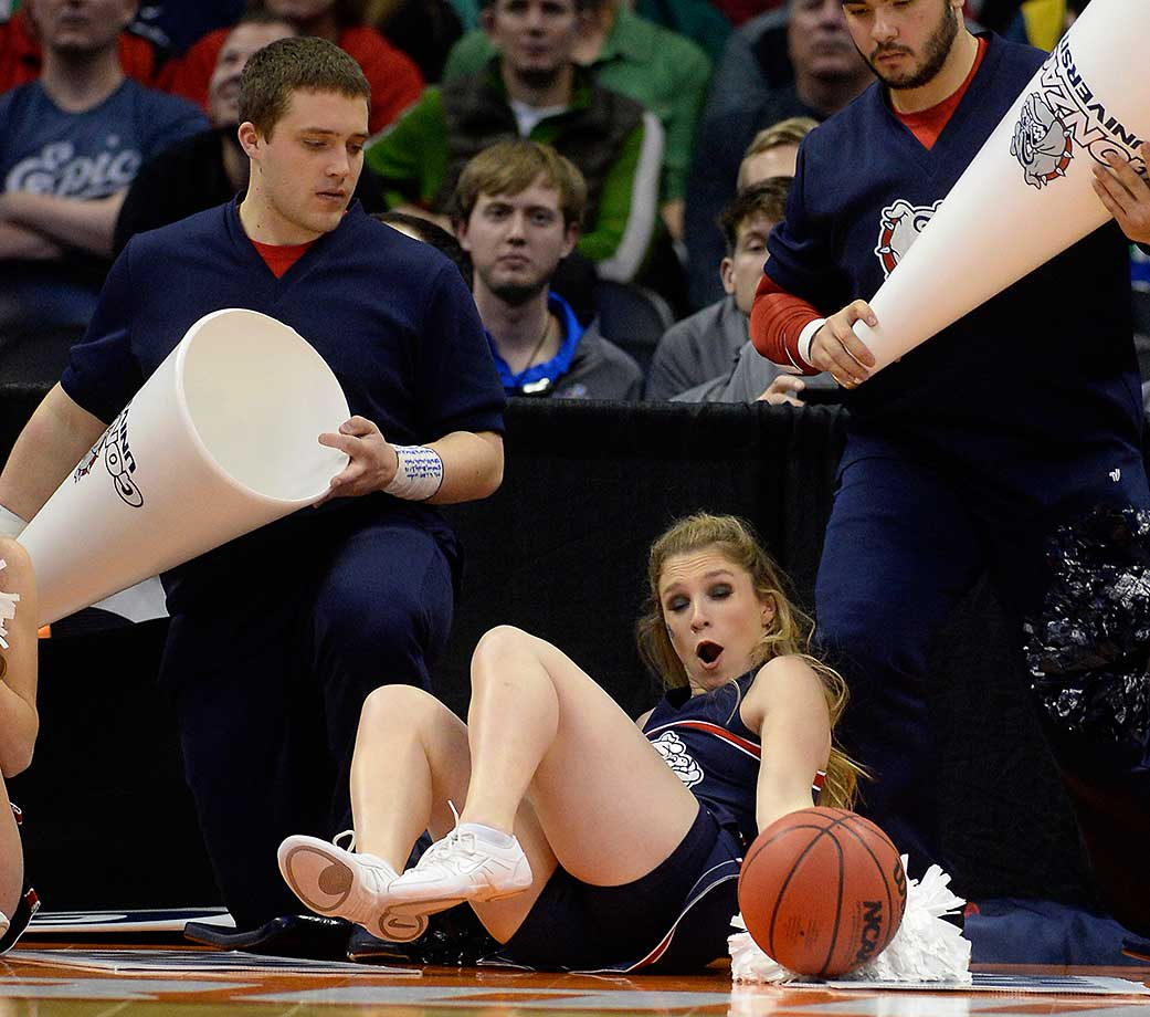 A Gonzaga cheerleader falls over as a ball bounces towards her.
