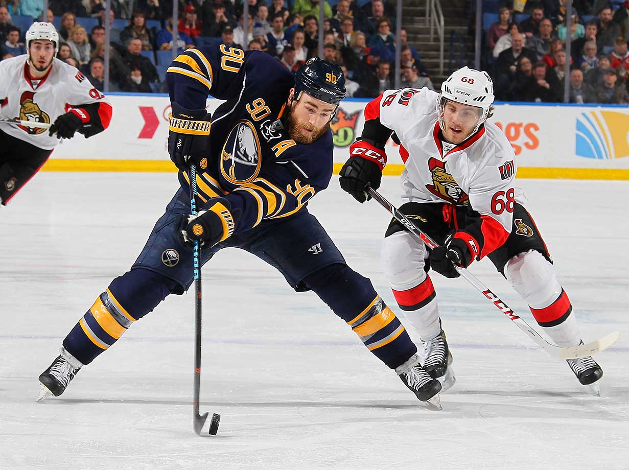 Ryan O'Reilly of Buffalo controls the puck while being pursued by Mike Hoffman of Ottawa.