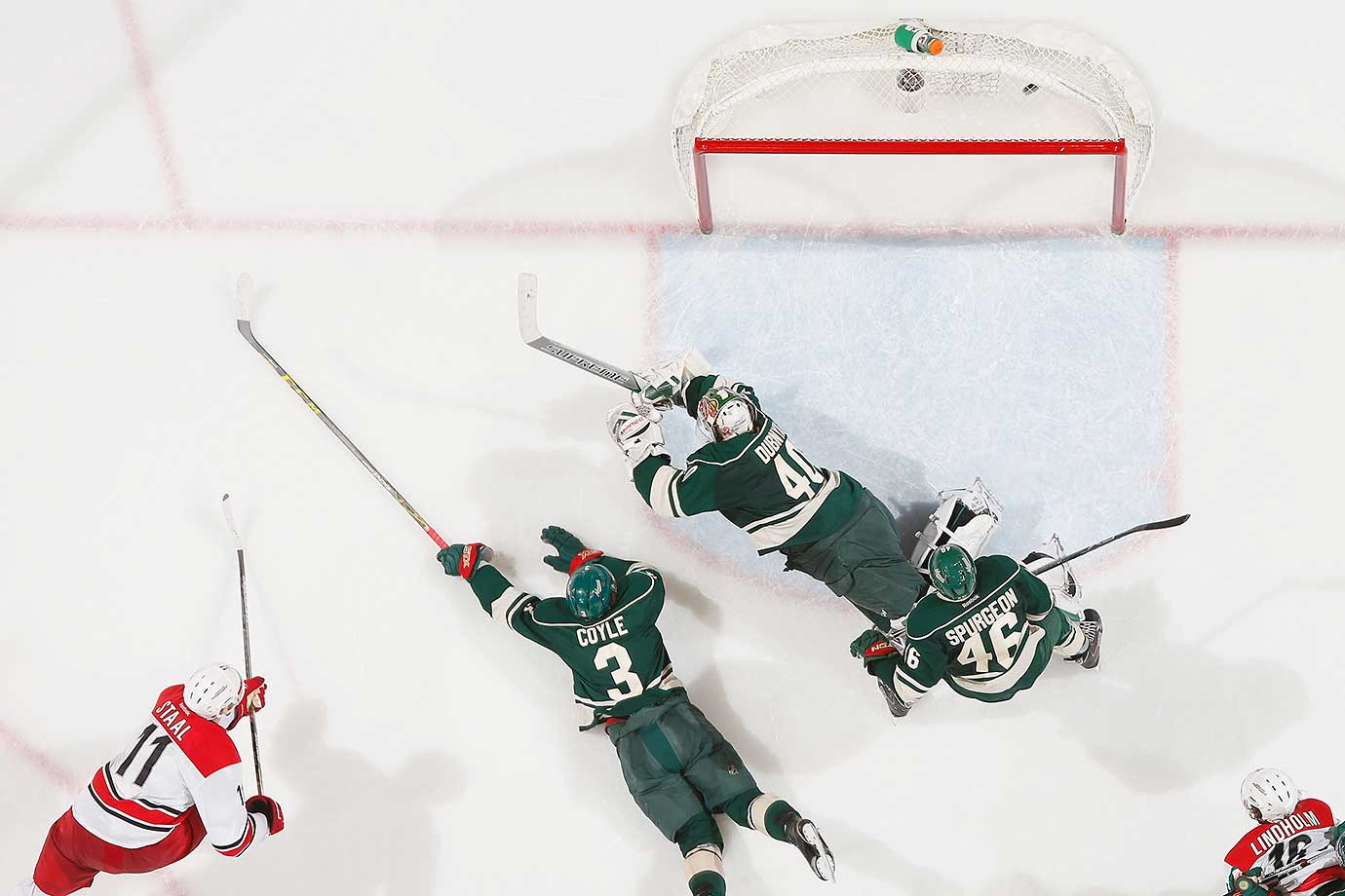 Jordan Staal of the Carolina Hurricanes scores a goal with Charlie Coyle, Devan Dubnyk and Jared Spurgeon of Minnesota defending.