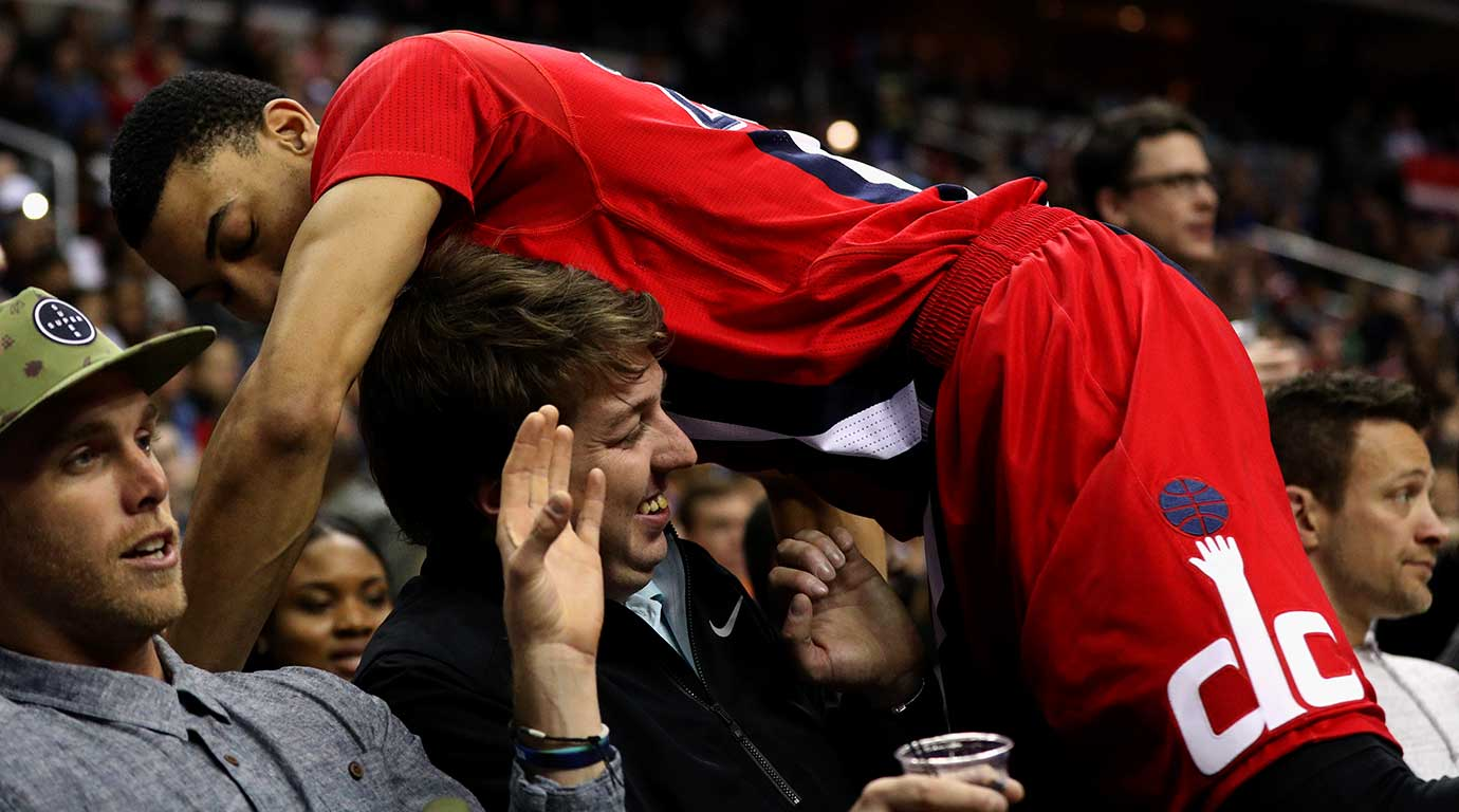 Otto Porter Jr. of Washington falls into a fan while going for a loose ball against the New York Knicks.