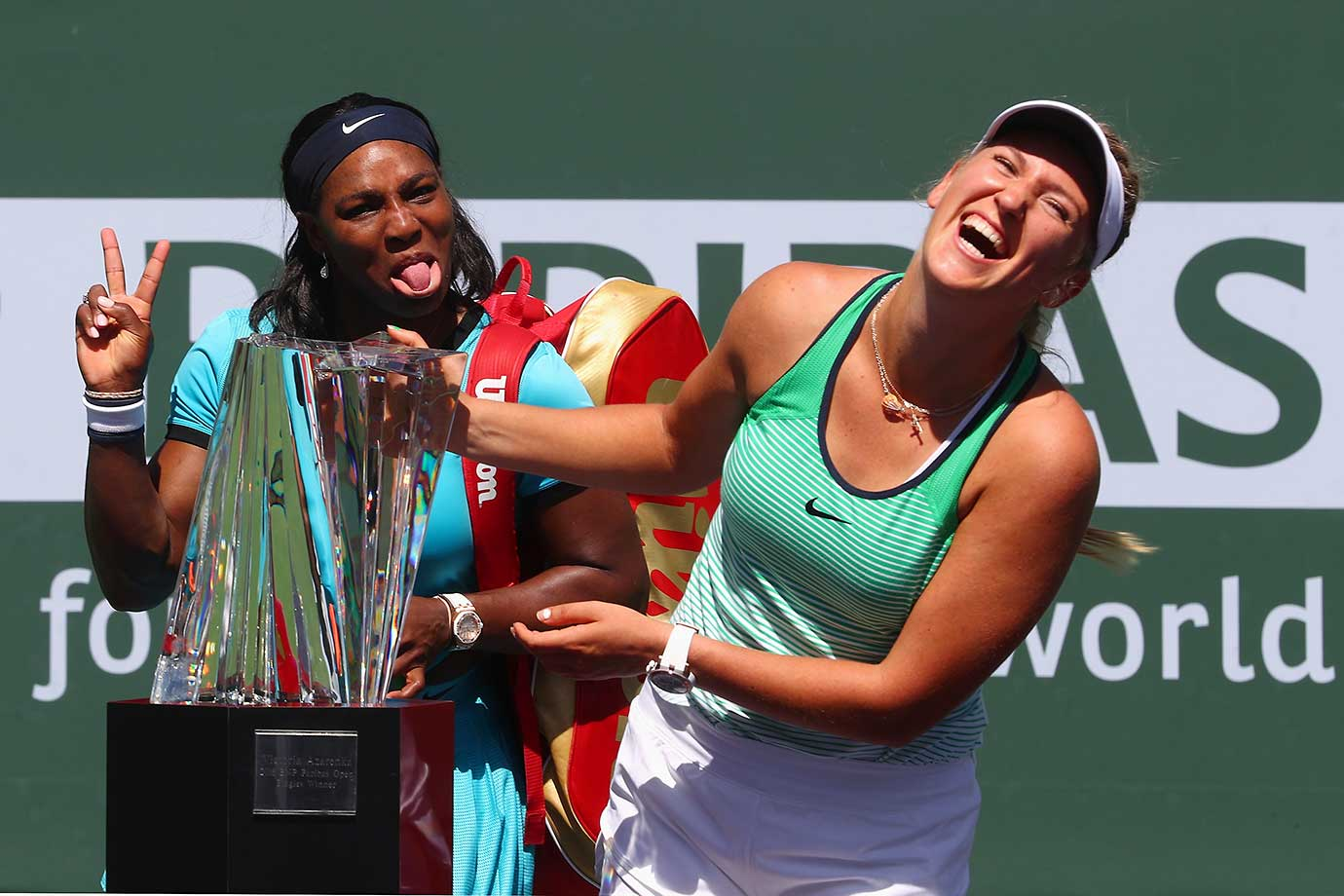 Victoria Azarenka of Belarus laughs with the winners trophy as Serena Williams pulls a face after the final in Indian Wells.
