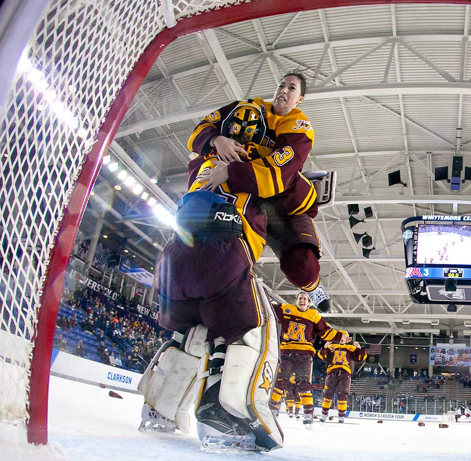 Milica McMillen of Minnesota jumps into the arms of Amanda Leveille after winning the Women's Hockey Frozen Four.