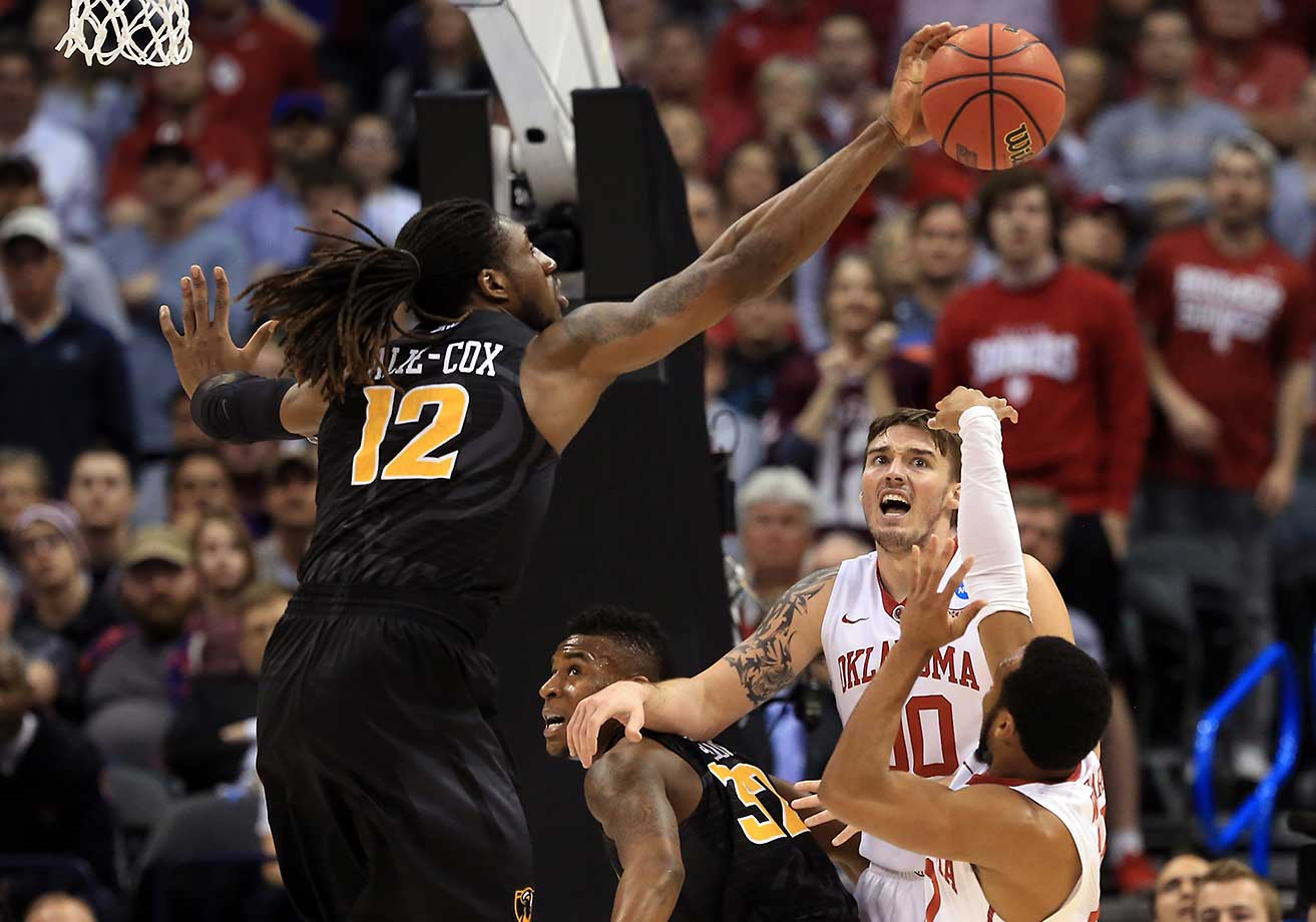 Mo Alie-Cox of VCU blocks a shot form Jordan Woodard of the Oklahoma Sooners.