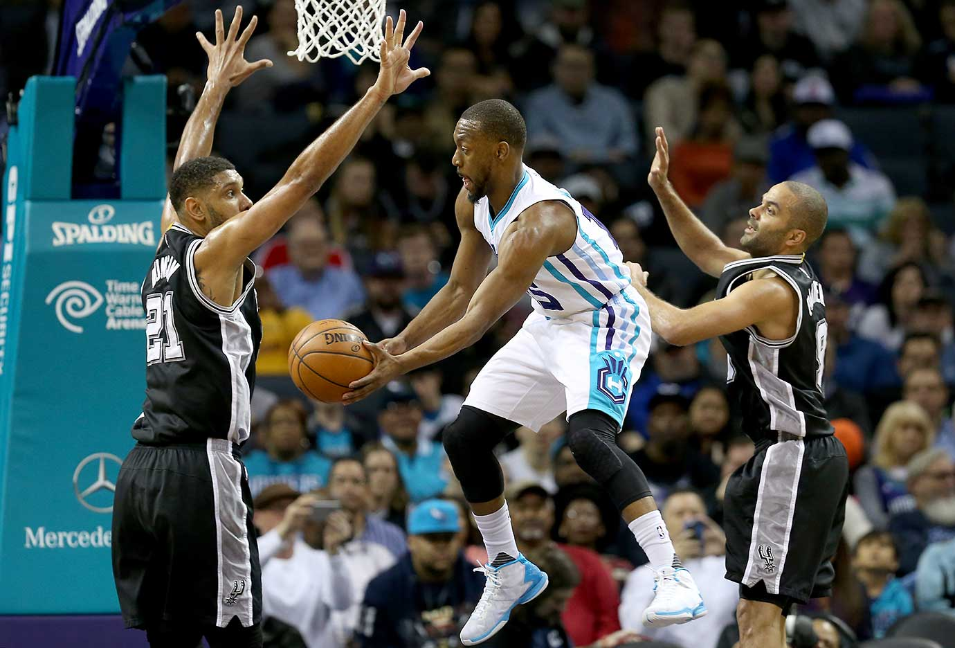 Kemba Walker of Charlotte looks to pass around Tim Duncan and Tony Parker of the San Antonio Spurs.