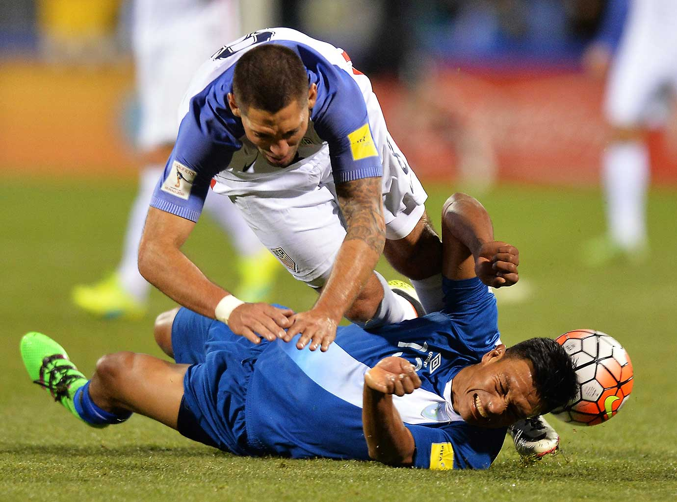 Clint Dempsey fall over Carlos Castrillo of Guatemala.