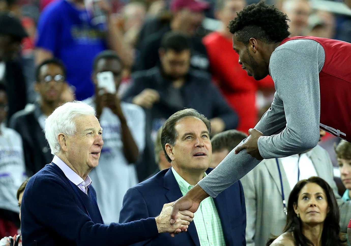 College basketball announcer Bill Raftery shakes hands with Buddy Hield of the Oklahoma Sooners as Jim Nantz looks on during a practice session for the Final Four in Houston.