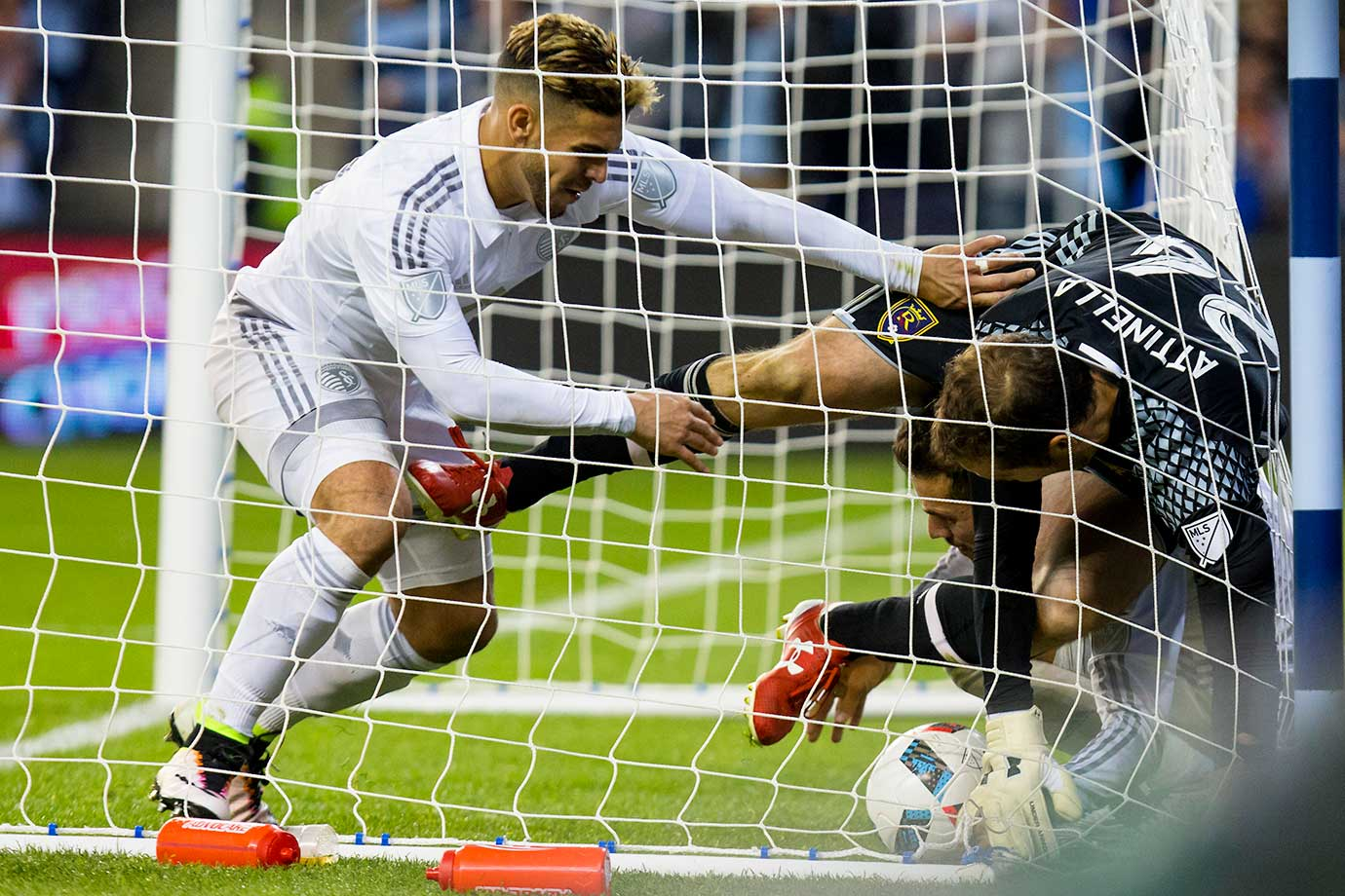 Dom Dwyer of Sporting Kansas City pushes Jeff Attinella of Real Salt Lake over Diego Rubio of Sporting Kansas City after Diego Rubio scored on a penalty kick.