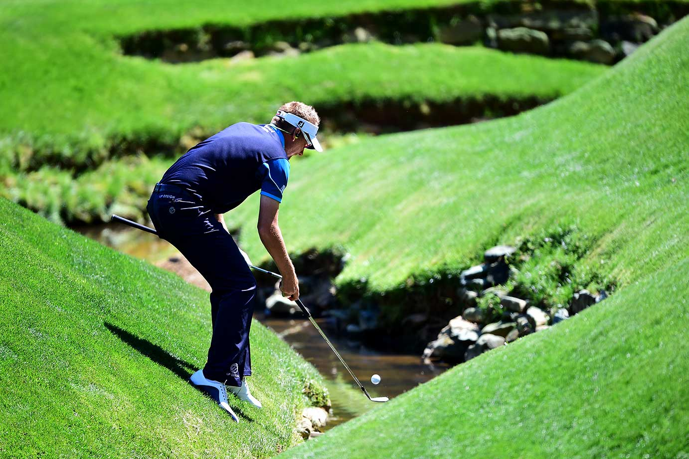 Ian Poulter of England retrieves his ball out of Rae's Creek during a practice round prior to the start of the 2016 Masters.