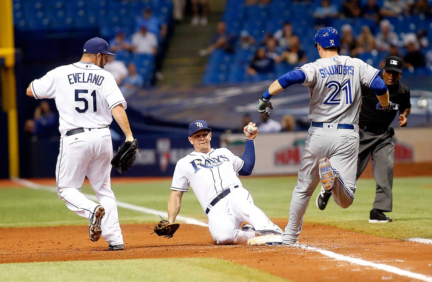 First baseman Logan Morrison of Tampa Bay gets the out at first base on Michael Saunders of Toronto as pitcher Dana Eveland runs in to back up the play.