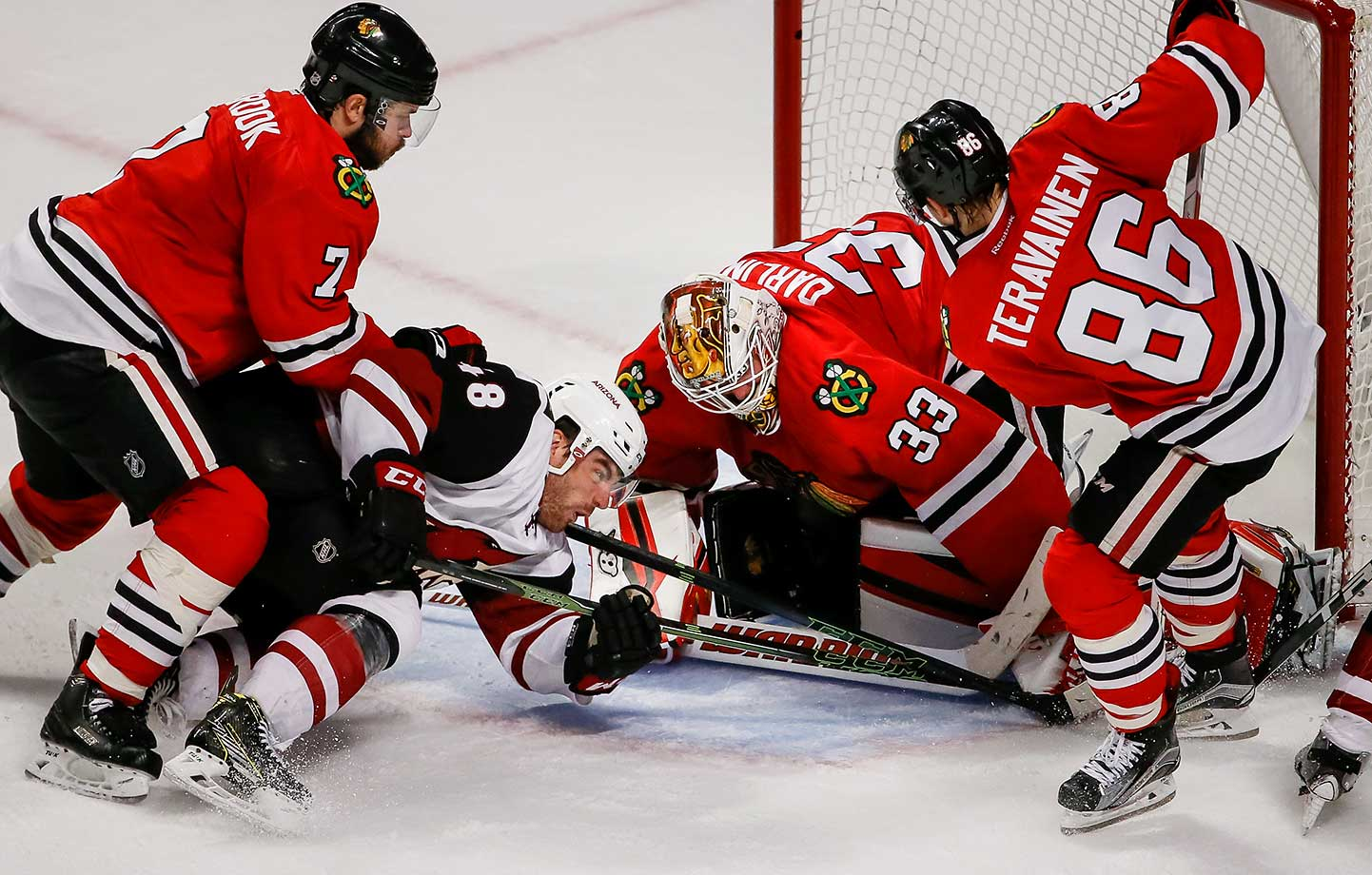 Jordan Martinook of the Arizona Coyotes attempts to get the puck past goalie Scott Darling of the Chicago Blackhawks.